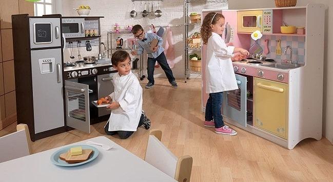 Niños jugando en cocinitas de juguete de madera